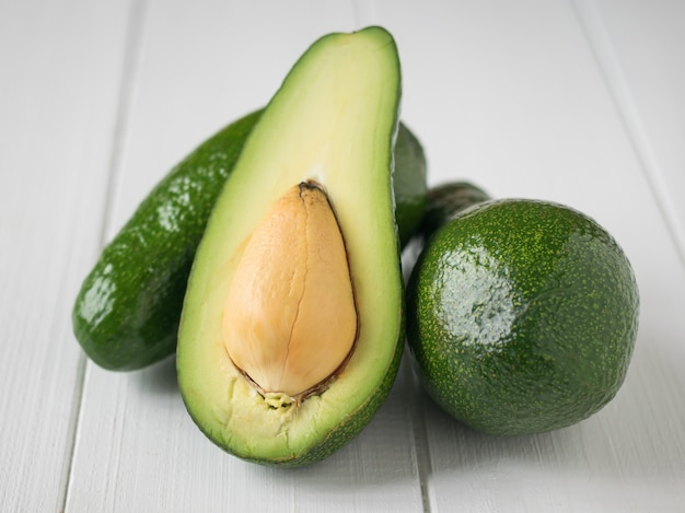 One cut and two whole avocados on white wooden table.