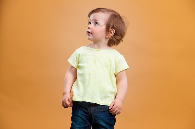 One cute baby girl on orange background