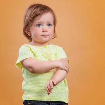 Una bambina carina sul muro arancione