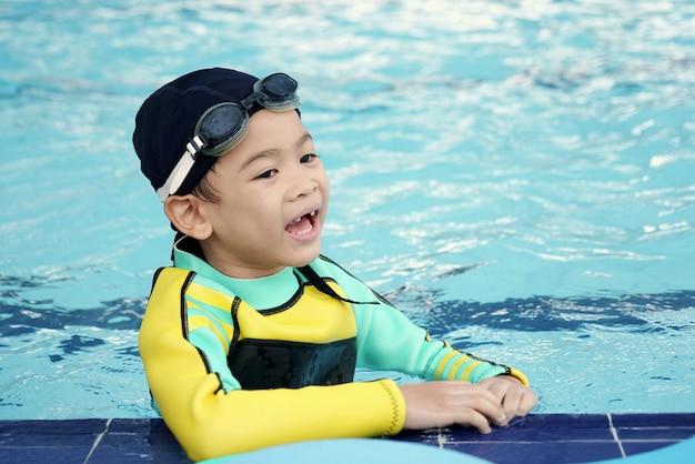 Один милый маленький мальчик smiley азиатский учит урок заплывания в открытом бассейне во времени деятельностей.