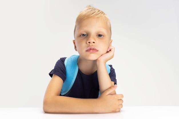 흰색 스튜디오 벽에 고립 된 한 귀여운 유치원 소년