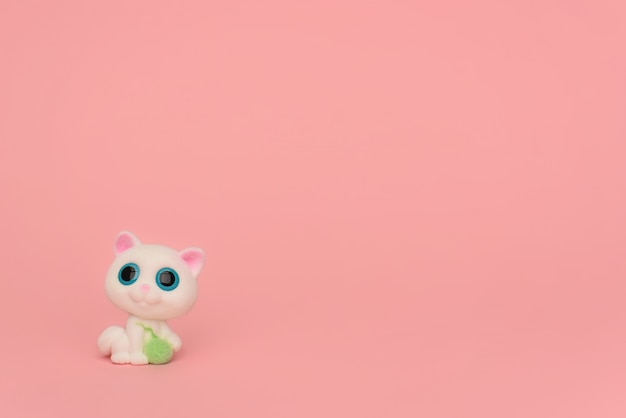 One cute white kitten with a ball of thread on a pink background. kids toy cat with big blue eyes and a ball of thread in its paws on pink. place for text. minimalism. sewing, needlework for children.