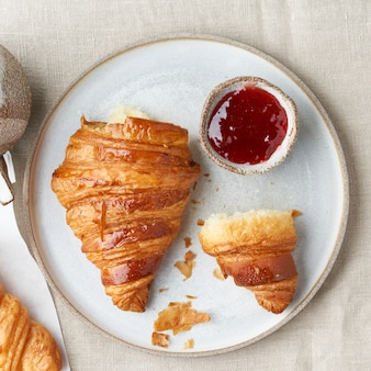 プレート上の1つのおいしいクロワッサン、マグカップで温かい飲み物。焼きたてのペストリーと朝のフランスの朝食