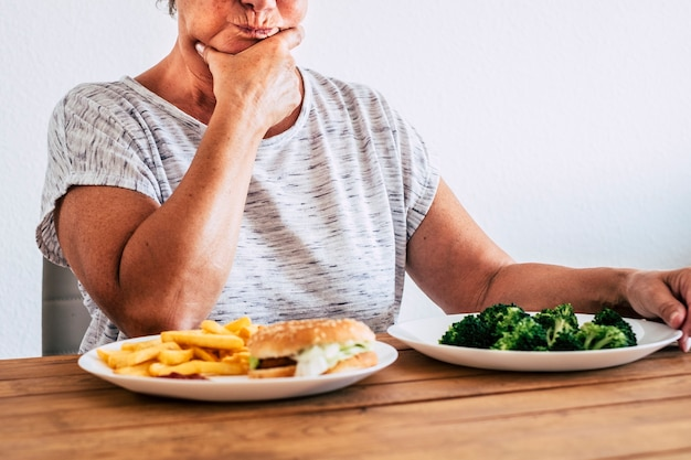 One disgusted old woman looking and eating healthy food at home dieting
