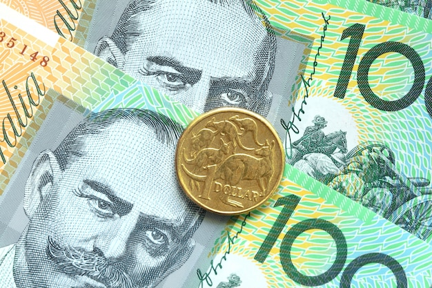 One dollar australian coins on one hundred banknote background