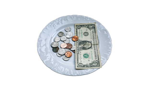 흰색 배경에 고립 된 접시에 누워 1 달러. 돈이 없는 사진. 가난한 사람들의 아이디어. 다임 및 센트 동전. 적은 급여와 연금으로 음식을 먹기에는 턱없이 부족합니다. 사회적 문제.