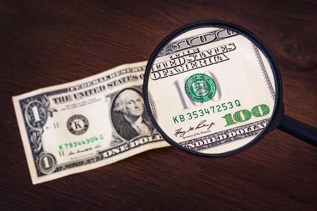 虫眼鏡の下の1ドルは100ドルのように見えます