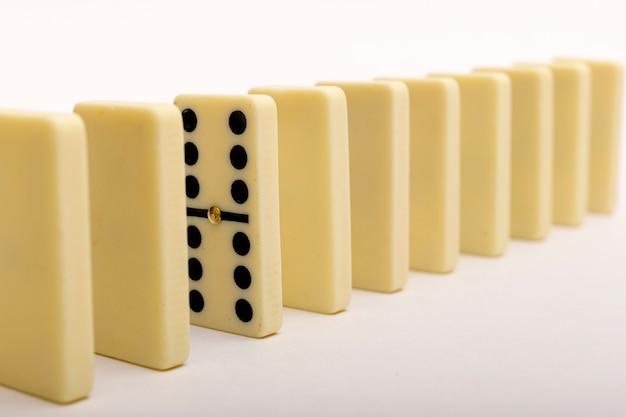 Одно домино выделяется из ряда. камни домино на белом