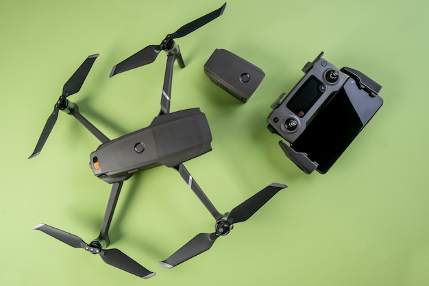 One drone, its controller and a smartphone on green surface seen from above.