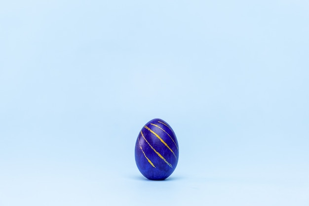 One easter egg trendy colored classic blue, white and golden on blue