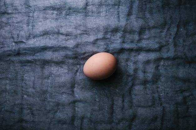 暗い生地の背景に1つの卵。イースター、春、またはエコフードのコンセプト。上面図