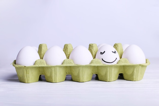 One egg in the tray is different smile,  happy easter  greeting card .