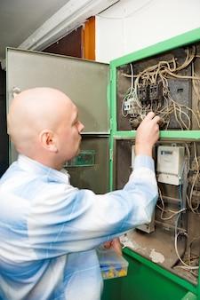 렌치 스패너를 사용하는 한 명의 전기 기사가 전기 상자의 나사를 조입니다.