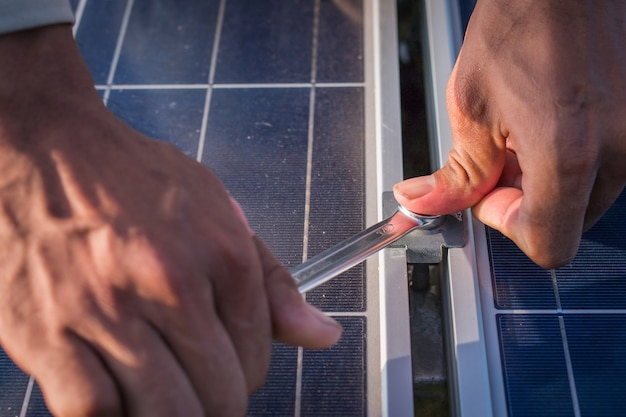 One electrician working on wrench tightening at solar mounting structure