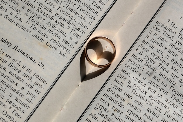 One elegant golden wedding ring jewel having heart shaped shadow symbol of love and unity on background of white page of bible book blessing day closeup, horizontal picture