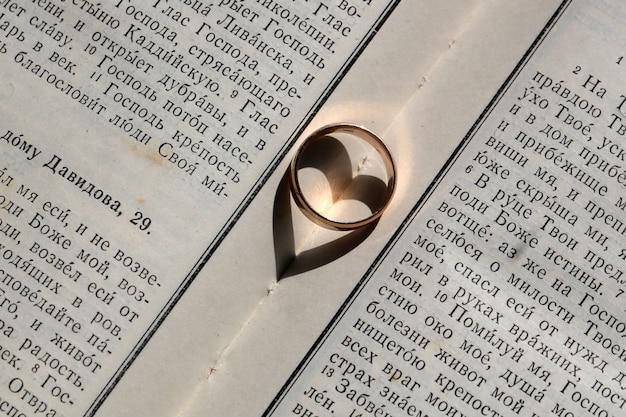 Одно элегантное золотое обручальное кольцо, имеющее теневой символ любви и единства в форме сердца на фоне белой страницы крупным планом дня благословения книги библии, горизонтальное изображение