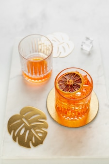 One empty and one full glass of aperol spritz cocktail. portrait orientation