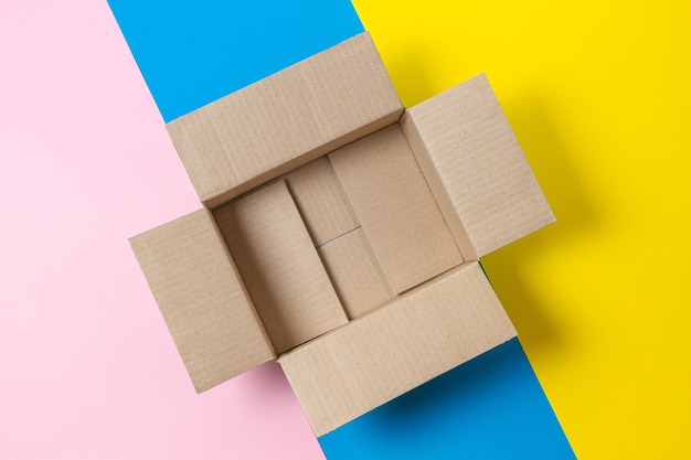 One empty open cardboard box on geometric pink, blue, yellow background. top view, copy space