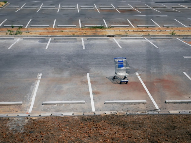 One empty shopping cart at empty parking lot of retailed store