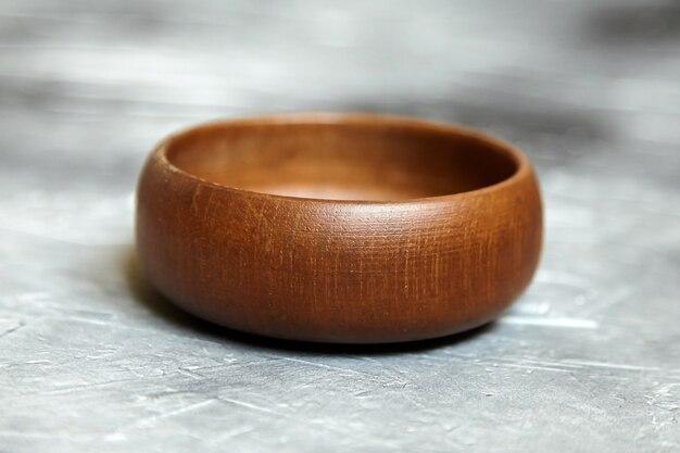 Одна пустая деревянная чаша на сером фоне. одиночная круглая салатница на каменном столе