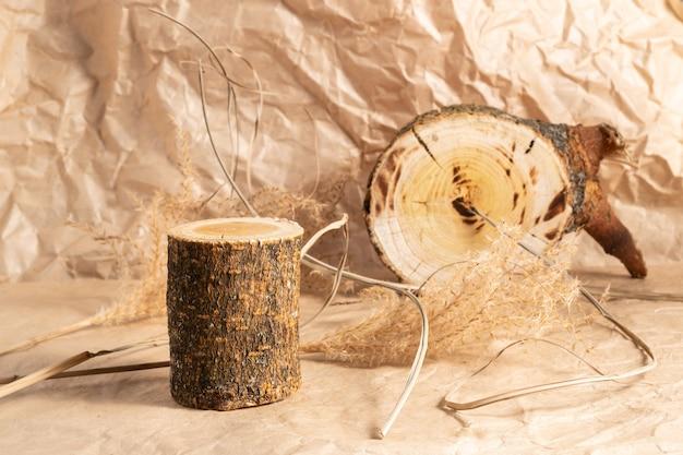 베이지 색 표면에 하나의 빈 나무 연단과 팜파스 잔디. 단색 디자인. 화장품 발표 용.