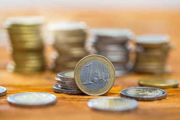 バックグラウンドで他の人が山に積み上げられたテーブル上の1ユーロ硬貨