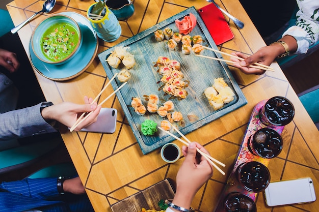 One family dinner holding the chopsticks on sushi set. flat lay, top view.
