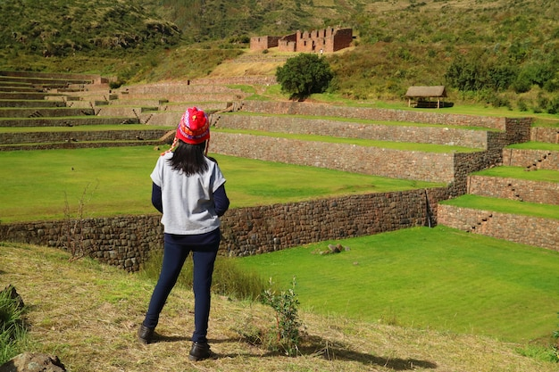 One female tourist looking at the impressive inca agricultural and irrigation ruins of tipon