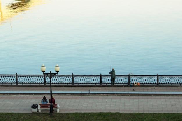 Один рыбак ловит рыбу на берегу городской реки ранней весной