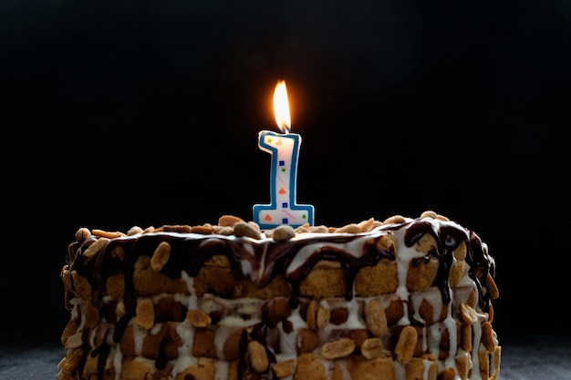 One flaming candle on birthday cake