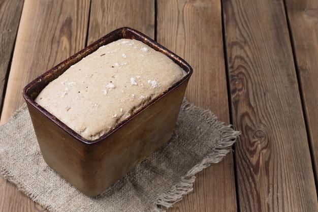Одна форма сырого ржаного и пшеничного хлеба с мучной закваской стоит на деревянном столе.