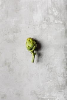 One fresh artichoke on a light gray table. exotic vegetable for healthy nutrition and diet