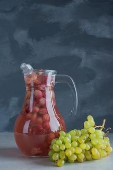 Un ramo d'uva fresco con una bottiglia di succo su sfondo scuro