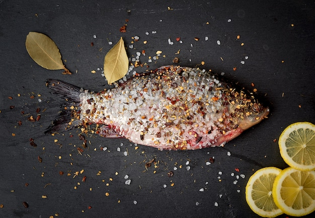 One fresh crucian fish sprinkled with spices lies on a black slate board