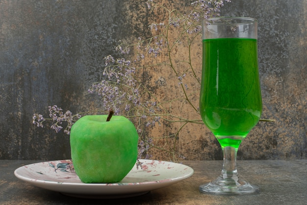 One fresh green apple with glass of green water on dark plate.