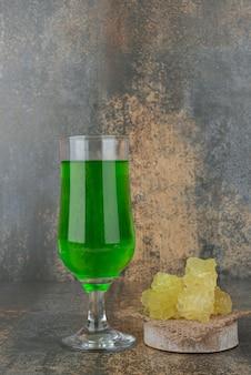 Один свежий зеленый стакан лимонада со сладким сахаром на мраморной поверхности