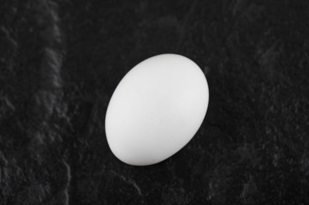 Одно свежее белое куриное яйцо на черном столе.
