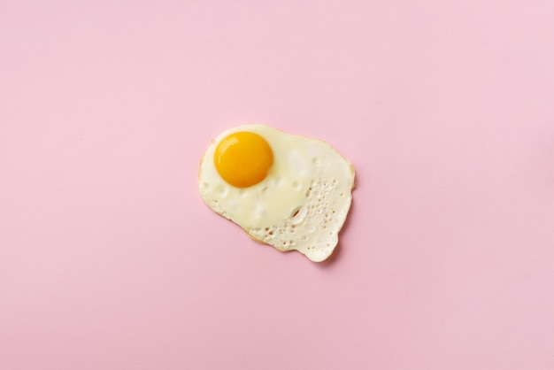One fried egg on pink paper background
