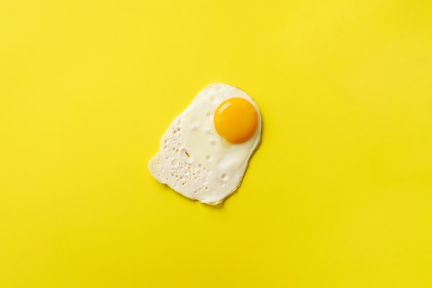 One fried egg on yellow paper background.