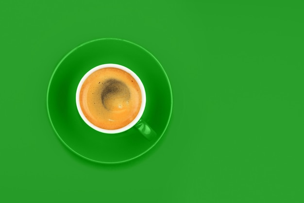 One full espresso coffee cup with saucer over vivid green paper background, elevated top view, directly above