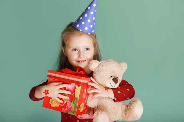 One funny happy child with present and bear toy dressed in birthday hat on the green background, sincerely smiling