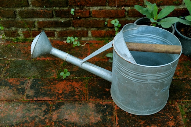 One galvanized watering can on the garden brick floor