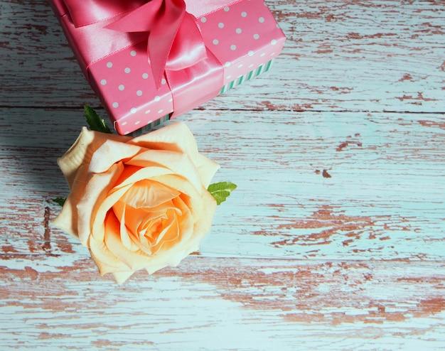 Одна подарочная коробка с розовым бантом на деревянном фоне, копия места для текста выросла рядом.