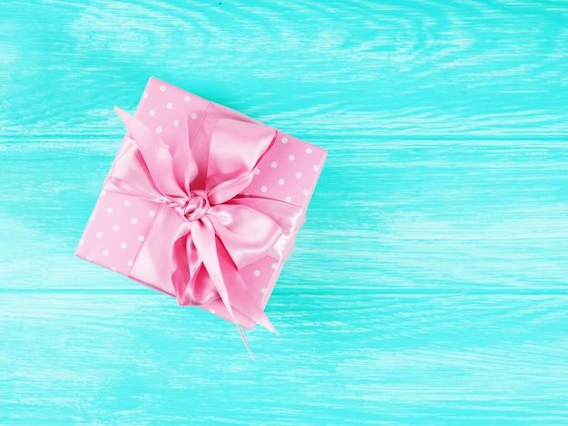 Одна подарочная коробка с розовым бантом на деревянном фоне, копия пространства для текста.