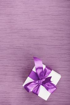 분홍색 바탕에 자주색 활과 하나의 선물 상자. 복사 공간이있는 세로