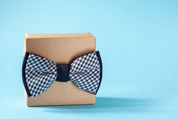 One gift box wrapped in craft paper and tied with the bow tie on blue background. concept father's day.