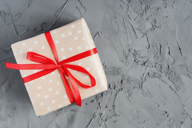 One gift box wrapped in polka dot craft paper with red ribbon on concrete background