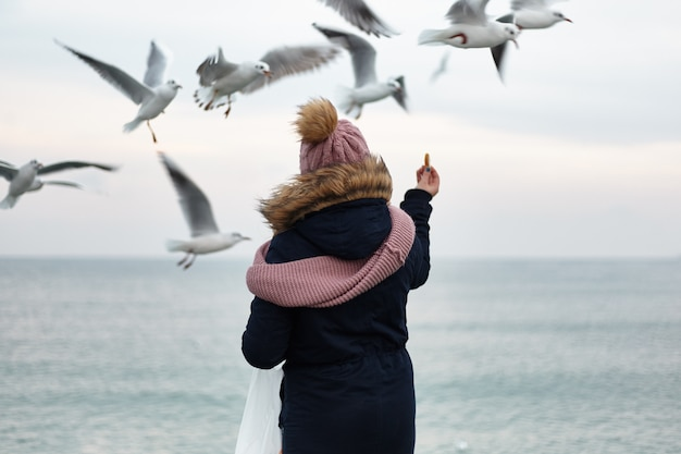 One girl in winter clothes are standing on the dock and feeding the gulls from their hands.