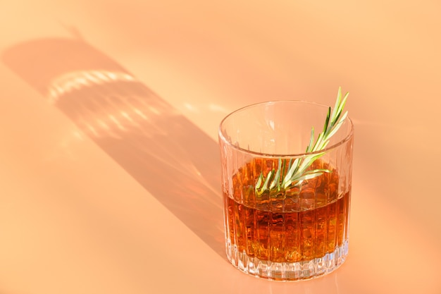 One glass of cold whiskey garnish rosemary on beige background with sunny shadow.