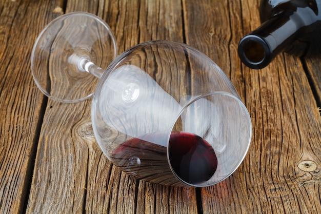 Один стакан половина красного вина на деревянный стол